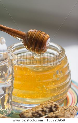 Spoon in Jar of honey on the table
