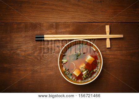 Bowl of delicious traditional japanese miso soup with wakame seaweed and tofu standing on wooden table surface with chopsticks lying near.