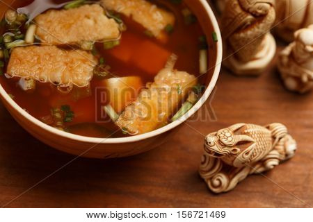 Bowl of tasty traditional japanese miso soup with fried tofu pieces stands at brown wooden table with dragon netsuke near and other netsuke at background. Shallow dof. Focus on tofu.