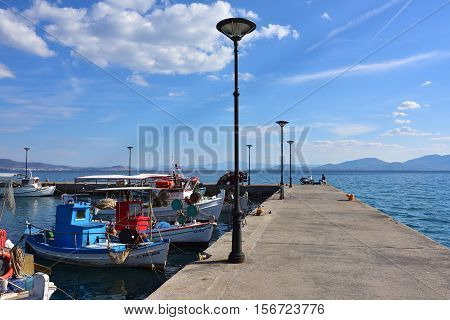 Paralia Politikon Greece- Sept 24 2016: Small fishing boats moored near pier at sunny warm evening. Aegean sea