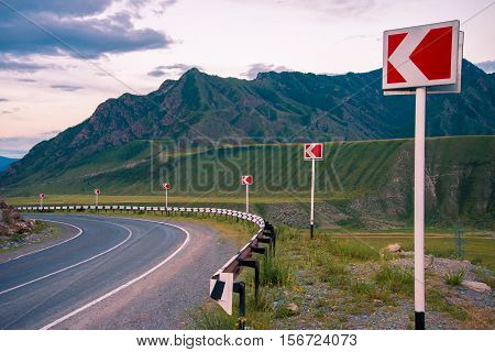 Landscape. The road in the mountains turns to the left. Ahead of breakage. Left turn sign.
