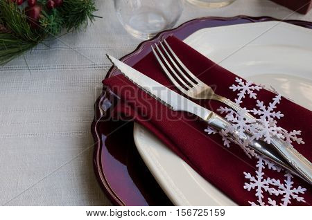 Beautiful decoration for festive dinner. Christmas table settings traditional bunch of fir tree wine red napkin with cutlery on white linen tablecloth. Copy space cutlery
