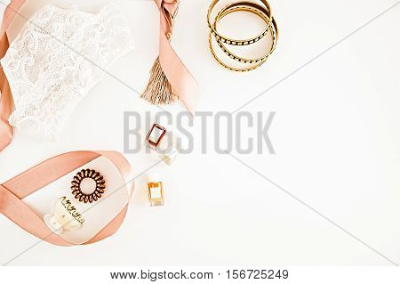 Flat lay for fashion blog and social media. Woman's glamour golden beauty accessories on a white background. Lingerie jewelry perfumes spiral hair ties and hair clips. Copy space for text. Horizontal