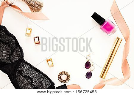 Flat lay for fashion blog and social media. Woman's glamour golden beauty accessories on a white background. Lingerie jewelry perfumes mascara pink nail polish spiral hair ties and hair clips. Copy space for text. Horizontal