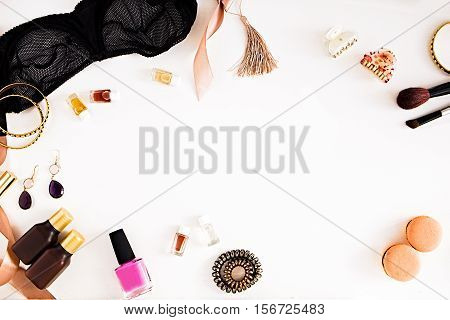 Flat lay for fashion and beauty blog and social media. Woman's glamour tools on a white background. Lace bralette jewelry perfumes spiral hair ties and hair clips nail polish mascara macaroons ribbon. Copy space for text. Horizontal