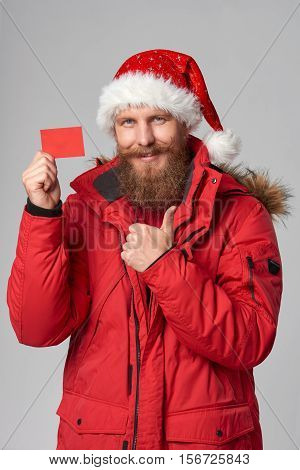 Smiling bearded man in red winter jacket and christmas hat showing blank credit card and gesturing thumb up, over grey background