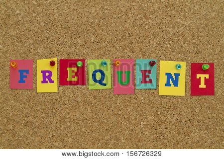 Frequent word written on colorful sticky notes pinned on cork board.