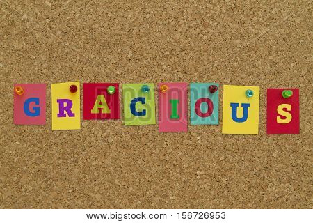 Gracious word written on colorful sticky notes pinned on cork board.
