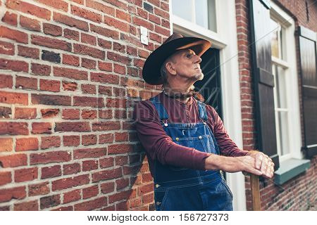 Senior farmer in dungarees with hat standing against wall of farm.