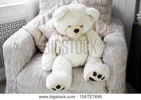 White Teddy bear. Room with white soft toy. Interior of the room in soft and light colours.