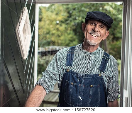 Vintage Smiling Senior Farmer Wearing Dungarees And Cap Entering Front Door Of Farm.