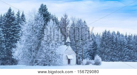 Christmas serene winter panoramic landscape with tiny woody chapel in snowy frozen forest