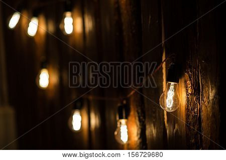 Vintage incandescent Edison type bulbs on wooden wall.