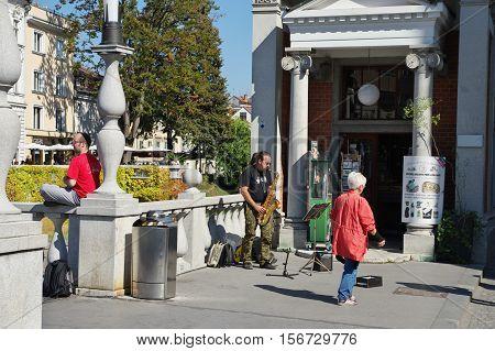 Ljubljana Slovenia - September 25 2016: City center. Saxophonist playing on the Triple Bridge.