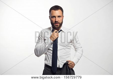 Emotional businessman loosen his tie on a gray background