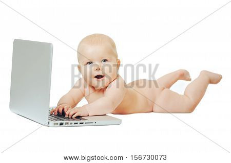 Happy little baby lying in front of a silver laptop and presses a button.