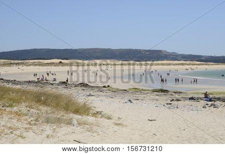 CORRUBEDA, SPAIN - AUGUST 10, 2016: People in a beach of natural dunes in Corrubedo Galicia Spain