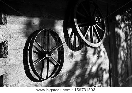 Vintage wheels various carts on the background of a wooden wall. Film noir style image.