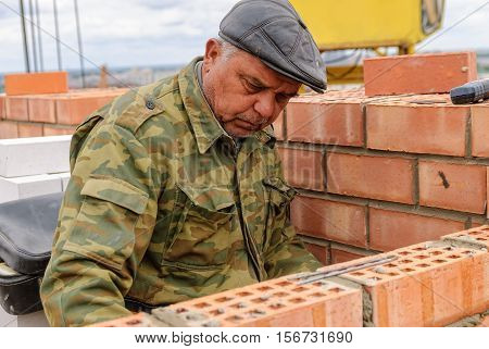 Tyumen, Russia - May 23, 2008: Bricklayer works on construction of 18 floor brick residental house at intersection of streets of Gercena and Chelyuskincev. Elderly bricklayer behind work