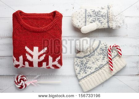 Winter holiday knitted sweater, mittens, cap and Christmas lollipops on white wooden background