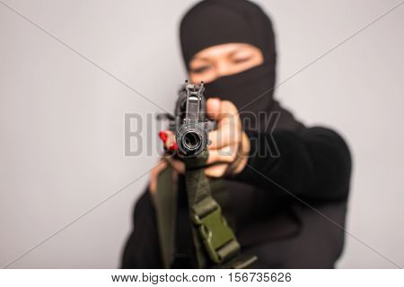 woman with machine gun. Armed female. Terrorist woman holding a submachine gun. Woman in black with gun