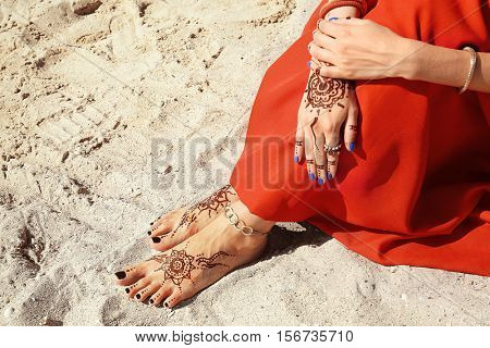 Female legs and hands with henna tattoo on beach sand background