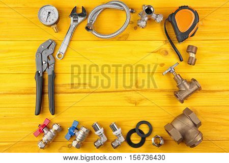 Plumber tools frame on yellow wooden background