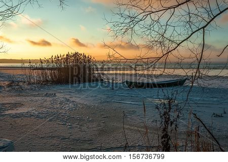 The wooden boat which froze in the first ice in warm colors of a cold decline