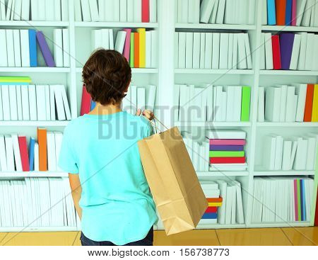 boy with paper bag in book store shop choosing books