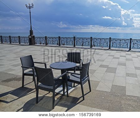 A table and four chairs on an empty seafront of the resort town of Sudak Crimea.