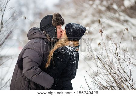 Young couple kissing on snowy winter day. They warmly clothed cap with ear-flaps.