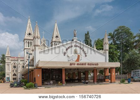 Dindigul India - October 23 2013: Saint Joseph Church. The entire church under blue sky. Front hall displays Jesus on frieze saying You live your life in presence of my love. Statue of Joseph and baby Jesus on top. Jesuit symbol in back.