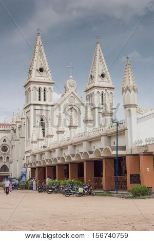 Dindigul India - October 23 2013: Saint Joseph Church. Lateral view shows the two white towers and their spires with the Jesuit symbol in the middle. Front hall rests on brown pillars.