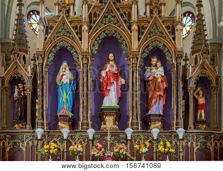 Dindigul India - October 23 2013: Inside Saint Joseph Church. Giant reredos behind altar has statues of Sacred Heart Jesus in center flanked by his parents Mary and Joseph each holding baby. Left Saint Anthony right Saint Sebastian.