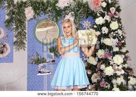 Christmas party, winter holidays blonde woman with gift box. New year girl. christmas tree in interior background