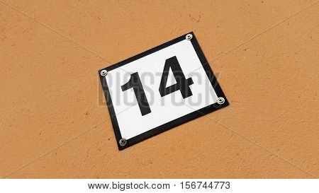 A house number sign with number fourteen isolated on a brown colored wall.