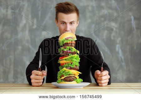 Man eating huge burger at table