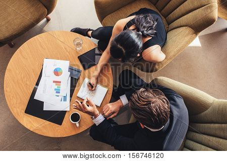 Two Business People Planning Work Around Table