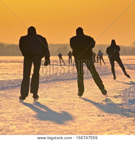 Ice Skaters On Frozen Lake At Orange Sunset