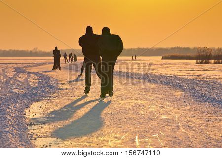 Ice Skaters On Frozen Lake Under Setting Sun