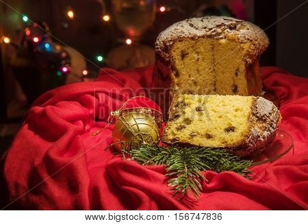 Cut Panettone, Green Branch, Baubles, Blurred Lights. Christmas Theme.