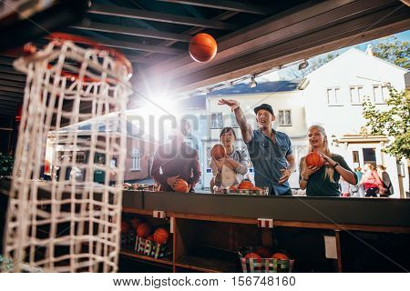 Group Of Friends Shooting Hoops At The Fair