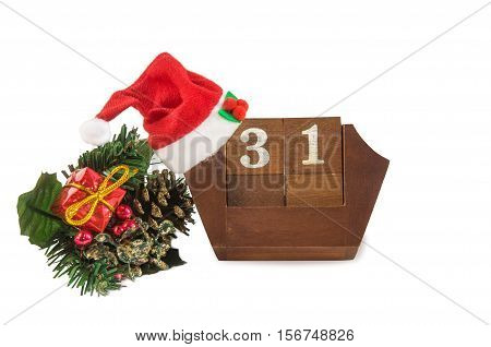 Cube shape vintage wooden calendar for December 31 with Santa hat Christmas decorations and gift box isolated over white. New year at work concept. Copyspace for text.