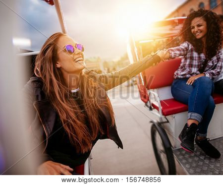 Young women having fun on two tricycles holding hands and smiling. Teenage girls riding on tricycle on road.