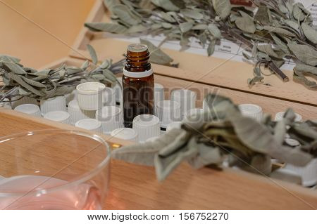 Brown glass bottle and other bottles in a wooden box behind it sage