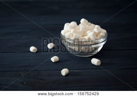 White Marshmallows In A Glass Bowl On Blue Wooden Background