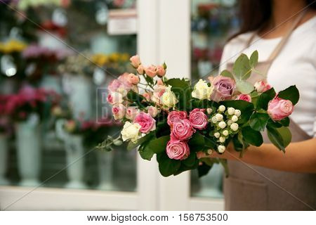 Young florist holding bouquet of flowers, close up view