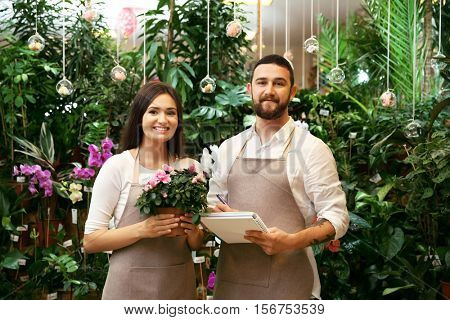 Florists with notebook, pen and azalea flower in greenhouse