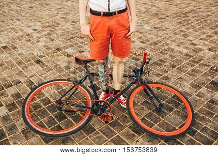 Red bycicle is on the square floor and boy with tattoo on his leg