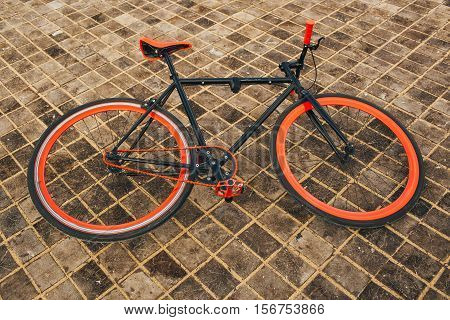Red bycicle is on the square floor side view